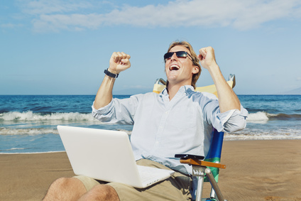 Young Attractive Man Celebrating Success, Working on Computer at the Beach